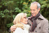 Old couple wearing warm clothes in the forest and expressing tenderness — Stock Photo