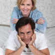 Married couple relaxing on bed — Stock Photo