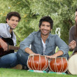 Stock Photo: Three young musicians in park