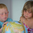 Little boy and girl looking at a globe — Stock Photo #9154314