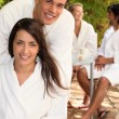 Couple with friends sitting on a terrace in toweling robes — Stock Photo
