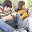 Two teens with guitar sat by tree — Stock Photo