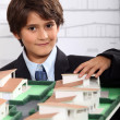 A little boy wearing suit and tie behind a district model — Stock Photo