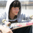 Stock Photo: Portrait of a smiling boy with a skateboard