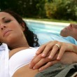 Couple lying by a pool - Stock Photo