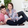 Young couple relaxing on sofa — Stock Photo