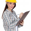 Female construction worker writing on her clipboard. — Stock Photo