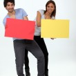 A young man and a young woman calling attention by showing panels — Stock Photo