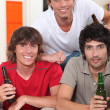Three 18 years old boys drinking beer at home - Stock Photo