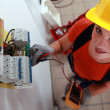 Stock Photo: Female electricichecking fuse box
