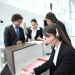 Female receptionist using a headset and laptop computer — Stock Photo