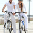 Couple riding bicycle wearing cycle helmet - Stock Photo