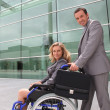 Woman in a wheelchair and man helping — Stock Photo