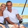 Couple doing sea fishing - Stock Photo