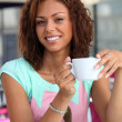 Half-breed damsel having coffee outdoors — Stockfoto