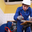 Young plumber cutting grey pipe — Stock Photo