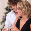 Intimate young couple drinking champagne at Christmas - Stock Photo
