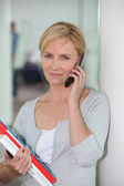Casually dressed office worker with a pile of paperwork talking on a cellph — Stock Photo