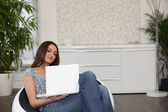 Woman using a laptop in a comfortable chair — Stock Photo