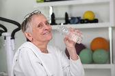 Anciana bebiendo agua embotellada en un gimnasio — Foto de Stock