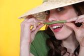 Playful woman holding a green bean above her upper lip — Stok fotoğraf