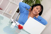 A middle age woman stretching in front of her computer. — Stock Photo