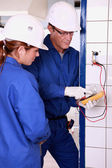 Electrician with female apprentice — Stock Photo