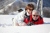 Older couple playing in the snow — Stock Photo