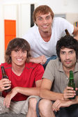Three 18 years old boys drinking beer at home — Stock Photo