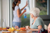 Senior woman having breakfast with home care in the background — Stok fotoğraf