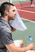 Tennis player sweeping out the sweat from his forehead — Stock Photo