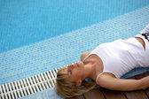 Blond woman laying poolside — Stock Photo