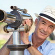 Man looking into a tower viewer - Stock Photo