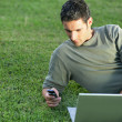 Man on the grass with laptop - Stock Photo