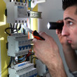 Stock Photo: Electrician examining a fusebox with a torch