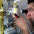 Electrician examining a fusebox with a torch — Stock Photo