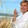 Woman drinking a glass of water by the seaside — Stock Photo