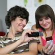 Teens looking at pictures on their mobile phones — Stock Photo
