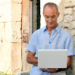 Older man using a laptop computer outside a lovely stone building — Stock Photo