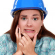 Stock Photo: Indecisive woman in a hardhat