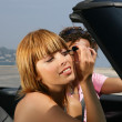 Woman putting on mascara in a car — Stock Photo