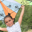 Little girl playing with a kite - Stock Photo