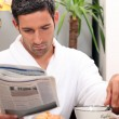 Stock Photo: Mhaving leisurely breakfast while reading paper