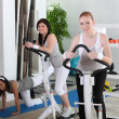 Young women using gym equipment — Stock Photo