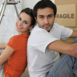 Couple sat by ladder and boxes — Stock Photo #9163937