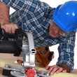 Carpenter with a circular saw - Stock Photo