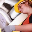 Tradeswoman reading a blueprint - Stock Photo