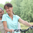 Stock Photo: Couple riding bikes in countryside