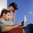Couple sat outside wuth laptop — Stock Photo