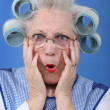 Stock Photo: Blue-eyed granny with giant hair curlers